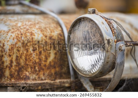 Detail close up of Rusty, colorful corroded metal of broken car wreck, old vehicle, with spotlight, copy space, blurred background.