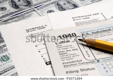 Detail closeup of current tax forms and pencil on money - stock photo