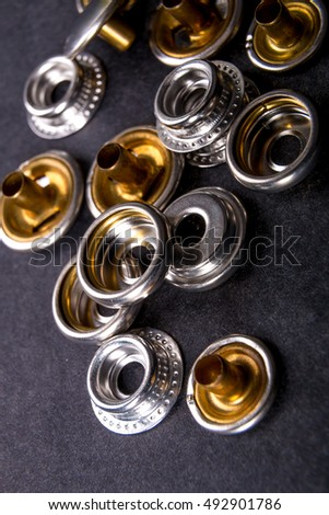 Detail for metal buttons for clothing on black background. Close up.