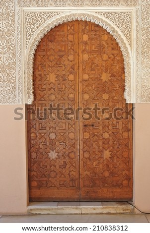 Detail form Alhambra palace in Granada, Andalusia - door made of carved wood - stock photo