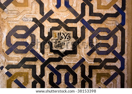 Detail from a wall in the Alhambra palace with interlocking tile work and an arabic centre piece. - stock photo