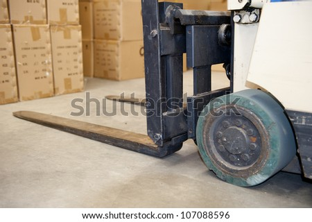 Detail image of fairly used forklift in warehouse, with boxes as blurred background. - stock photo