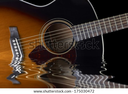 detail of a acoustic guitar on reflective water surface in black back
