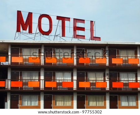 """Detail of a an old """"MOTEL"""" sign atop an old motel with many rooms. - stock photo"""