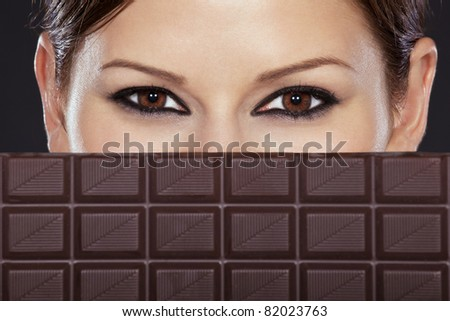 Detail of a beautiful woman's face half covered with chocolate bar