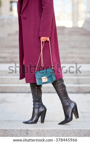 Detail of a beautiful young fashion woman wearing colorful coat and high heel shoes with handbag in the city streets . Street style .