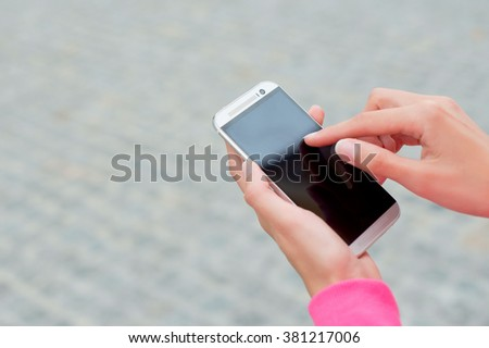 Detail of a beautiful young woman holding a phone in his hand . Outdoor . - stock photo