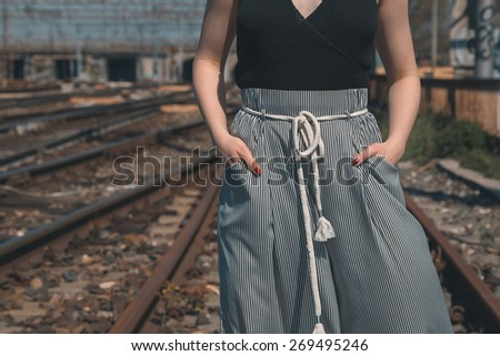Detail of a beautiful young woman in trousers posing along railroad tracks - stock photo