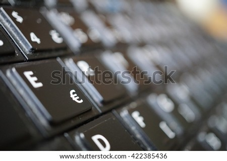Detail of a black dusty laptop keyboard with a focus on a sign of Euro currency