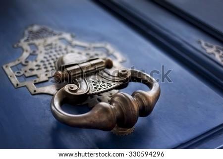 Detail of a bronze knocker on a wooden door - stock photo