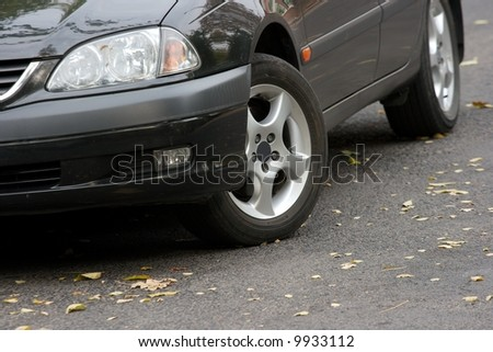 Detail of a car on the road with some fallen leaves