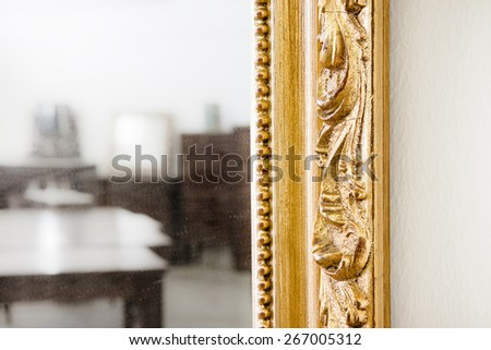 Detail of a carved and golden wooden frame  - stock photo