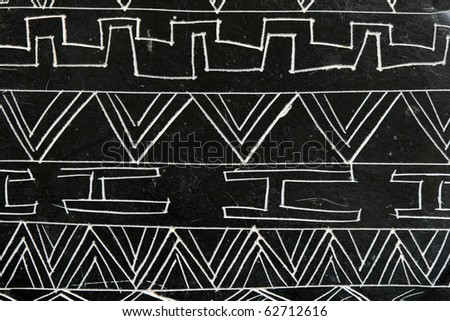 detail of a carved soapstone object with abstract patterns in white on black - stock photo