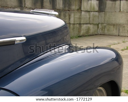 Detail of a circa 1940 classic American car against a background of large, aged, cement blocks. The same blocks are reflected in the finely polished curves of the fender and hood. - stock photo