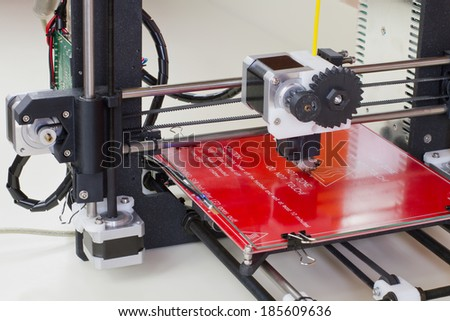 Detail of a 3D printer with a yellow plastic filament