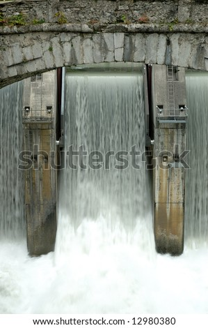 Detail of a dam on the river Simme in the Bern canton in Switzerland. The picture shows the powerful waters flowing from the dam and shot from underneath an old bridge's arch. - stock photo