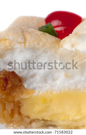 Detail of a delicious traditional homemade lemon ,meringue pie decorated with a cherry and angelica. - stock photo