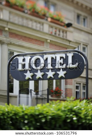 "Detail of a four stars hotel with beautiful building in the background. Tilt shift lens used to accent the word ""hotel"" and to emphasize the background - stock photo"