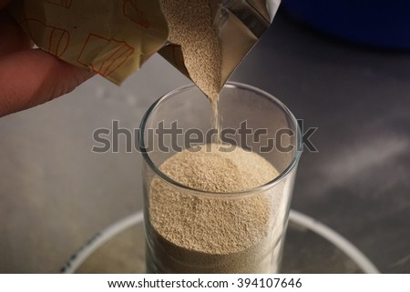 Detail of a glass filled with yeast (leaven) standing on the small scale during the last phase of a beer brewing - stock photo