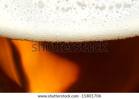 Detail of a glass of beer with a lot of foam - stock photo
