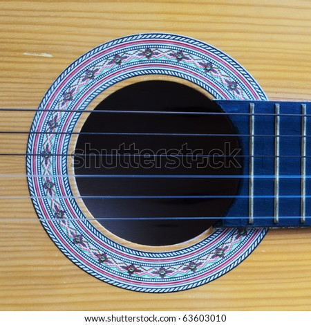 Detail of a guitar showing the sound box and strings - stock photo