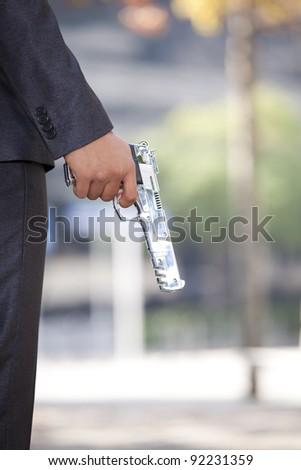 Detail of a hand holding a gun - stock photo