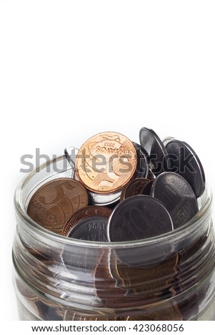Detail of a jar full of Brazilian coins isolated on white background - stock photo