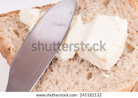 Detail of a knife spreading (spread) cheese on a bread slice onto a white background