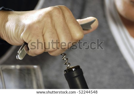 detail of a man's hand broaching a bottle of wine - stock photo