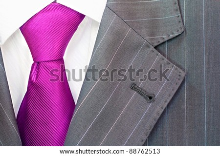 Detail of a man's striped business suit.Pink or purple tie and a shirt - stock photo