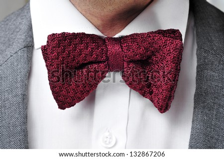 detail of a man wearing a gray jacket suit, white shirt and maroon bow tie - stock photo