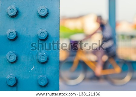 Detail of a Metal Bridge Pole with a Girl Riding a Bicycle in the Background - stock photo