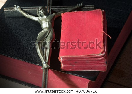Detail of a metallic crucifix (Christ on the cross) with two Holy Bibles - stock photo