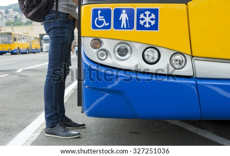 Detail of a modern city public transport  bus and a passenger getting on.