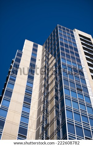 Detail of a modern high-rise multilevel building with right angles, with dark blue glass windows with metal frames and walls overlaid with natural beige travertine, with the prospect of a blue sky - stock photo