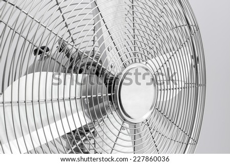 Detail of a modern metal electric fan with shiny blades. - stock photo