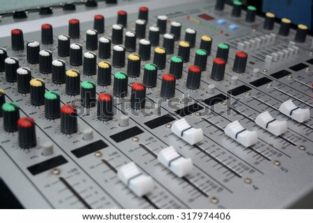 Detail of a music mixer desk with various knobs or slides. shallow depth of field