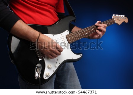 Detail of a musician playing a black electric guitar.