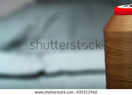 Detail of a needle with thread in the workroom reel of thread, and natural fabric. Work table of a tailor. Sewing textile or cloth. Shallow depth of field. Focus on reel of thread - stock photo
