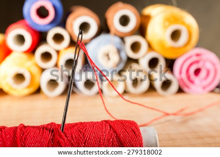 detail of a needle with thread in the workroom,shallow depth of field - stock photo