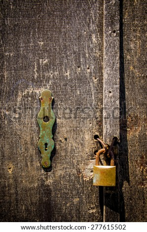 Detail of a old scratched wooden door with rusty padlock - stock photo