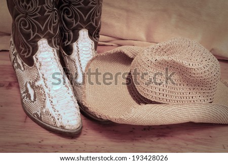 Detail of a pair of black leather with python skin cowboy boots and floppy straw hat on rustic wooden table of cedar. There is a soft golden backdrop. Vignette is added for a vintage atmosphere. - stock photo