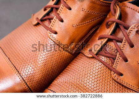 Detail of a pair of brown luxurious men's leather shoes.