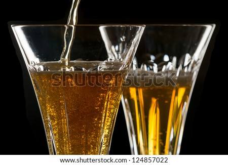 Detail of a pair of cut glass champagne goblet with a heart on the side and drink being poured - stock photo