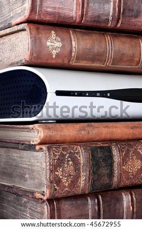 Detail of a piece of electronic equipment in a pile of old leather bound books - stock photo