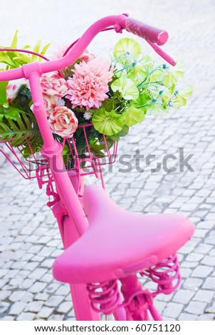 Detail of a pink painted bicycle with a basket with flowers and leaves - stock photo