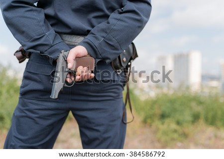 Detail of a police officer holding gun. Selective focus with shallow depth of field. - stock photo