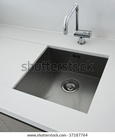 detail of a rectangular designer kitchen sink with chrome water tap - stock photo