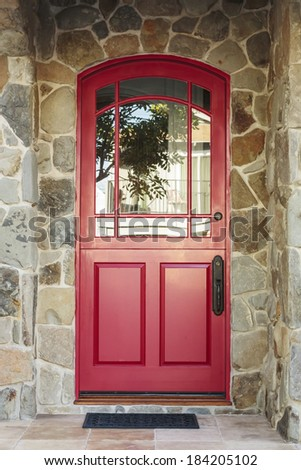 Detail of a red front door to a home in daytime. The door is arched with glass windows, and is framed by the house's stone detail. Also seen is greenery, a doormat, and the reflection of a tree.  - stock photo