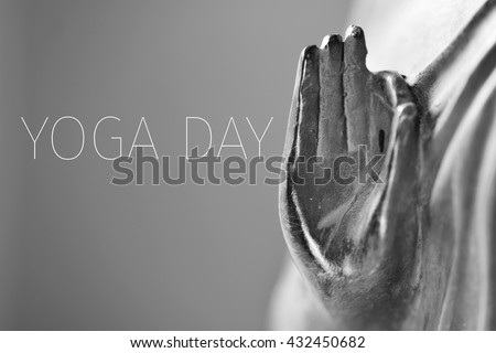 detail of a representation of the Buddha with his hand in gyan mudra in duotone and the text yoga day - stock photo
